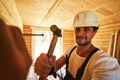 Diligent builder hammering in a nail into wooden wall - PhotoDune Item for Sale