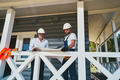 Pair of construction engineers reading drawings on porch - PhotoDune Item for Sale