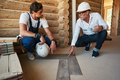 Construction engineer telling builder how to lay parquetry - PhotoDune Item for Sale