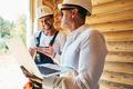 Civil engineer with laptop explaining something to housebuilder - PhotoDune Item for Sale