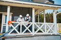 Two male workers on porch inspecting technical document - PhotoDune Item for Sale