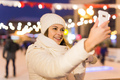 Christmas, winter, technology and leisure concept - happy young woman taking picture with smartphone - PhotoDune Item for Sale
