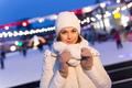 Happy young woman in winter near the ice rink. Christmas and winter concept - PhotoDune Item for Sale