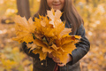 Close up of little girl holds a bouquet of autumn leaves in her hands in fall season - PhotoDune Item for Sale