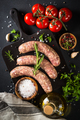 Bratwurst or sausages on cutting board with spices at black table - PhotoDune Item for Sale