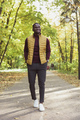 African american student walking in the park in autumn season - PhotoDune Item for Sale
