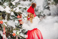 A girl in a white jacket and red hat dresses up a Christmas tree in the forest in winter.A girl - PhotoDune Item for Sale