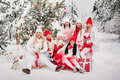 A large group of girls with Christmas gifts in their hands standing in the winter forest.Girls in - PhotoDune Item for Sale