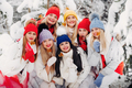 A large group of girls with lollipops in their hands stands in the winter forest.Girls in red and - PhotoDune Item for Sale
