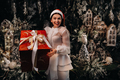 a girl in a Santa hat with a big Christmas gift in her hands on a fairy-tale island.Smiling woman in - PhotoDune Item for Sale