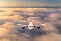 Airplane is flying above the clouds at sunrise in summer - PhotoDune Item for Sale