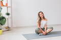 Positive girl sitting on fitness mat resting after pilates or yoga practice. Mindfulness and - PhotoDune Item for Sale