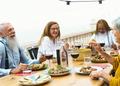 Multiracial seniors dining together at home terrace - Elderly people having at dinner on house patio - PhotoDune Item for Sale