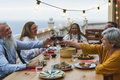 Multiracial senior friends having fun dining together and toasting with red wine on house patio - PhotoDune Item for Sale