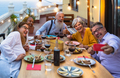 Happy multiracial senior friends having fun dining together while taking selfie with mobile phone - PhotoDune Item for Sale