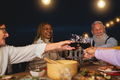 Happy multiracial senior friends toasting with red wine glasses together on house patio dinner - PhotoDune Item for Sale