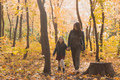 Young woman and her child girl walking through autumn park. Single parent and motherhood concept - PhotoDune Item for Sale