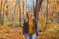 Girl holds fallen leaves and walks in autumn park. Seasonal concept - PhotoDune Item for Sale