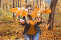 Happy laughing young woman throwing leaves in autumn park. Fall season - PhotoDune Item for Sale
