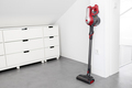 Modern Cordless vacuum cleaner leaning on a wall of a room - PhotoDune Item for Sale