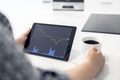 Woman looking at a digital tablet with stock market chart - PhotoDune Item for Sale