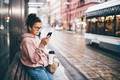woman with glasses and mobile phone waits for bus and gets into salon on public transport stop - PhotoDune Item for Sale