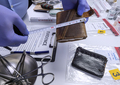 Specialised police officer measures wallet in crime lab, conceptual image - PhotoDune Item for Sale