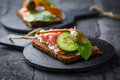 Open sandwich with prosciutto on black bread (pumpernickel) on cutting board - PhotoDune Item for Sale