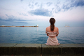 Lonely young woman sitting by the ocean - PhotoDune Item for Sale