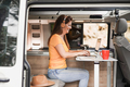 Mature woman working inside mini van camper with computer laptop wearing wireless headphone - PhotoDune Item for Sale