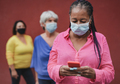 Multiracial women waiting in a line while wearing safety face maks for coronvirus - PhotoDune Item for Sale