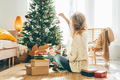 Woman decorating Christmas tree at home. - PhotoDune Item for Sale