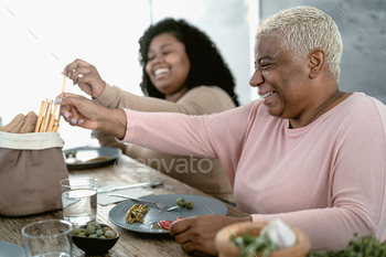 Happy Hispanic mother and daughter having healthy lunch at home