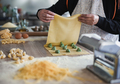 Mature woman preparing fresh made ravioli with ricotta cheese and spinach inside pasta factory - PhotoDune Item for Sale