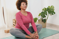 Mature multiracial woman doing yoga stretching exercises at home - PhotoDune Item for Sale