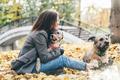 Women hugging dog in the autumn park. - PhotoDune Item for Sale