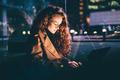 Woman using laptop on night city street. - PhotoDune Item for Sale