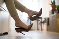 Woman feeling pain after wearing high heels shoes all day long at work taking footwear off at home - PhotoDune Item for Sale