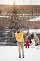 Happy guy enjoy skating on ice rink in snowfall. Cheerful man has fun outdoors on street ice-rink - PhotoDune Item for Sale