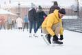 Man on ice rink tying shoelace of skates skating on open ice-rink outdoors on Christmas holidays - PhotoDune Item for Sale