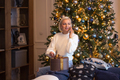 Happy woman call to husband thankful for gift on Christmas or New year sit with box near Xmas tree - PhotoDune Item for Sale