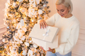 Christmas morning at home: happy young woman open gift box sitting at Xmas tree at New year eve - PhotoDune Item for Sale