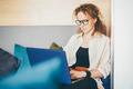 Woman in eyeglasses working using laptop, female working in modern studio. - PhotoDune Item for Sale