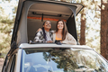 Multiracial women enjoy road trip vacation with mini van camper and looking out on roof top - PhotoDune Item for Sale