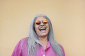 Senior woman wearing hippie sunglasses while laughing on camera - Gray hair granny smiling - PhotoDune Item for Sale