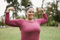 Curvy woman posing in front of camera showing muscle biceps - PhotoDune Item for Sale