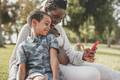 African mother and mixed race son using mobile phone at city park - PhotoDune Item for Sale
