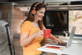 Mature woman using computer laptop inside mini van camper while drinking coffee - PhotoDune Item for Sale