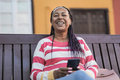 Old african woman sitting on a bench in the city and smiling on camera while holding mobile phone - PhotoDune Item for Sale
