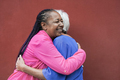 Old multiracial women meet and hugging each other with red background - PhotoDune Item for Sale